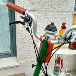 Brown bottle cage on handlebar with bicycle bottle